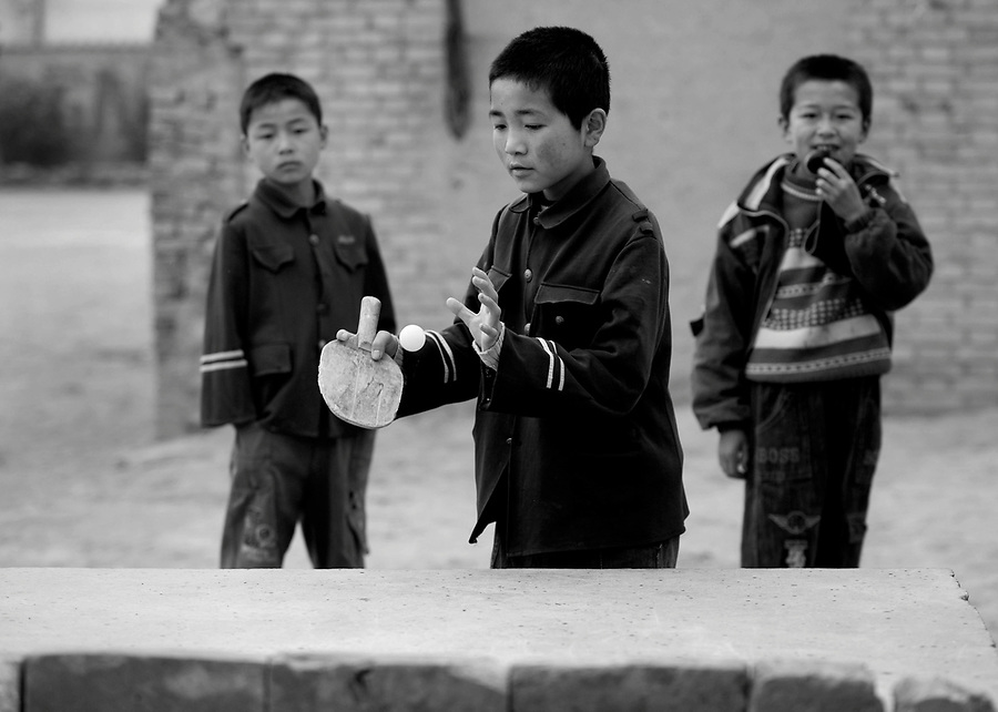 """A boy in a 'Mao"""" jacket plays table tennis during a class break in Chuanhua county in China's poor Shanxi Province."""