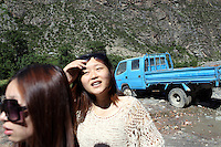 Two Chinese women walking by the side of the road in Sichuan Province, western China.