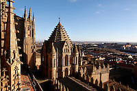 View from the roof, New Cathedral, Salamanca, Spain, pictured on December 19, 2010. The elaborate Baroque carvings are lit by the winter afternoon sunshine with a view of the city in the background. To the right is the scallop-tiled  Torre del Gallo (Cock Tower), a ribbed umbrella lantern in the Byzantine style. Salamanca, Spain's most important University city,  has two adjoining Cathedrals, Old and New. The old Romanesque Cathedral was begun in the 12th century, and the new in the 16th century. Its style was designed to be Gothic rather than Renaissance in keeping with its older neighbour, but building continued over several centuries and a Baroque cupola was added in the 18th century. Restoration was necessary after the great Lisbon earthquake, 1755. Picture by Manuel Cohen