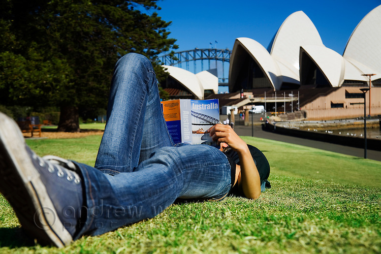 A female tourist reads her guidebook in front of the Sydney Opera House.  Sydney, New South Wales, AUSTRALIA.