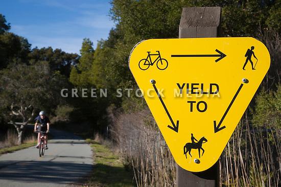 Right of way sign with a bicyclist in the background at the Sawyer Camp Trail. San Mateo, California, USA