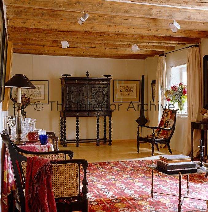 A dark carved cabinet stands at one end of this living room which features Ikat textiles and a large kilim rug
