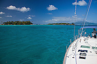 Man steering yacht in lagoon