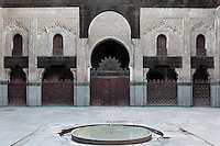 Low angle view of central courtyard with pool in the foreground, Bou Inania Madrasa, Fez, Morocco, pictured on February 22, 2009 in the evening. The Bou Inania Madrasa was founded as a boarding school and mosque in AD 1351-56 by Abu Inan Faris, also the founder of the Bou Inania Madrasa in Meknes, and holds the status of Grand Mosque. A fine example of Marenid architecture with its intricate plasterwork, carved cedar and decorated tiles or zellij it is the only mosque in Fez open to non-Muslim visitors. It was renovated in the 18th and 20th centuries. Fez, Morocco's second largest city, and one of the four imperial cities, was founded in 789 by Idris I on the banks of the River Fez. The oldest university in the world is here and the city is still the Moroccan cultural and spiritual centre. Fez has three sectors: the oldest part, the walled city of Fes-el-Bali, houses Morocco's largest medina and is a UNESCO World Heritage Site;  Fes-el-Jedid was founded in 1244 as a new capital by the Merenid dynasty, and contains the Mellah, or Jewish quarter; Ville Nouvelle was built by the French who took over most of Morocco in 1912 and transferred the capital to Rabat. Picture by Manuel Cohen.