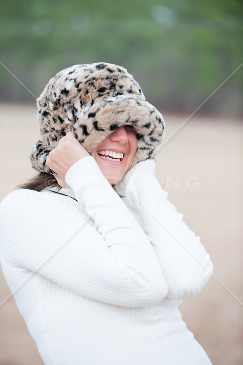 Young woman pulling her fur hat down over her ears and eyes, with a big toothy smile