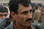 A man appears worried as he waits to apply for a job as a police officer in Kirkuk, Iraq. Officials sought to fill 1,300 slots for the next training class, but were overwhelmed when more than 4,000 applicants showed up. More than half were turned away at the gate, and hundreds of others waited in line for hours, but never got a chance to submit their papers. The event was shut down after a U.S. advisor observed an Iraqi recruiting officer take a bribe from an applicant. Dec. 6,  2007. DREW BROWN/STARS AND STRIPES