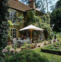 A table has been laid for lunch under a parasol in the garden of this Victorian rectory