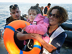 Volunteers carriy a girl to safety as a rubber raft lands on a beach near Molyvos, on the Greek island of Lesbos, on October 30, 2015. The boat, which came from Turkey, was filled with refugees who paid Turkish traffickers huge sums for the trip. They were received in Greece by local and international volunteers, then proceeded on their way toward western Europe.