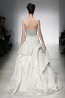 Model walks runway in an Alana wedding dresses by Amsale Aberra, for the Kenneth Pool Spring 2012 Bridal runway show.