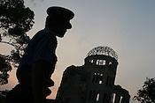 A policeman stands beside the Atomic Dome Memorial in Hiroshima, Japan, on Friday Aug. 5th 2005. The Dome is a memorial to the atomic bombing of the city of Hiroshima, on 6th August 1945, during World War 2. The bomb was the first atomic bomb to be used in warfare, and was dropped by the US military.