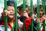 Asia, China, Guangxi, Daxu. School children rush to the gate to greet tourists passing through the streets of their ancient town of Daxu.