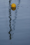 A buoy is framed perfectly in a reflection of a sail mast at Fort Baker Harbor in Sausalito, California.
