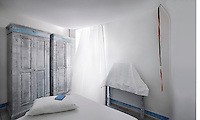 The simply furnished and decorated white bedroom has an airy and monastic feel