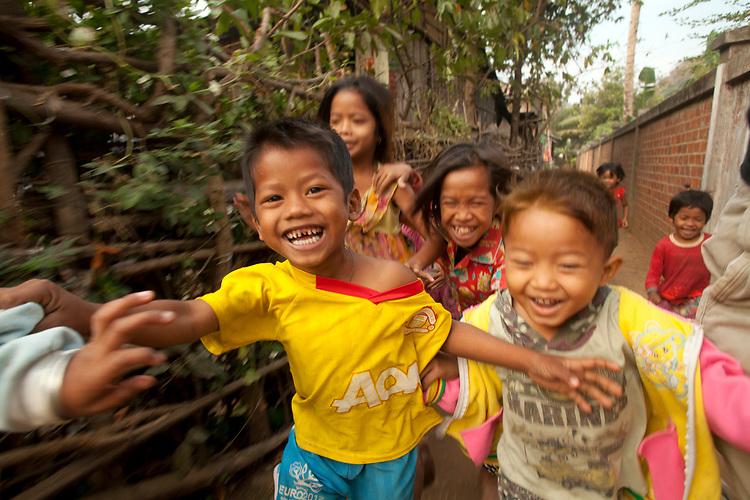 Young children run through a small village near Battambang, Cambodia. <br /> <br /> Photos &copy; Dennis Drenner 2013.
