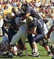 Pittsburgh defense gang tackles Virginia Tech running back Kevin Jones on November 3, 2001.