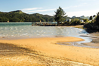Golden sand of Whanganui Inlet and jetty on west coast of South Island, Nelson Region, New Zealand