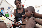 Dr. Gaspar Gaston (unseen) checks a small patient in a tent clinic set up on a street in Jacmel, a town on Haiti's southern coast that was ravaged by the January 12 earthquake.
