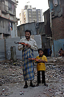 In the early morn a father and son pose with toy rifles.