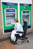 Older woman wheelchair user using a cashpoint machine.  MR