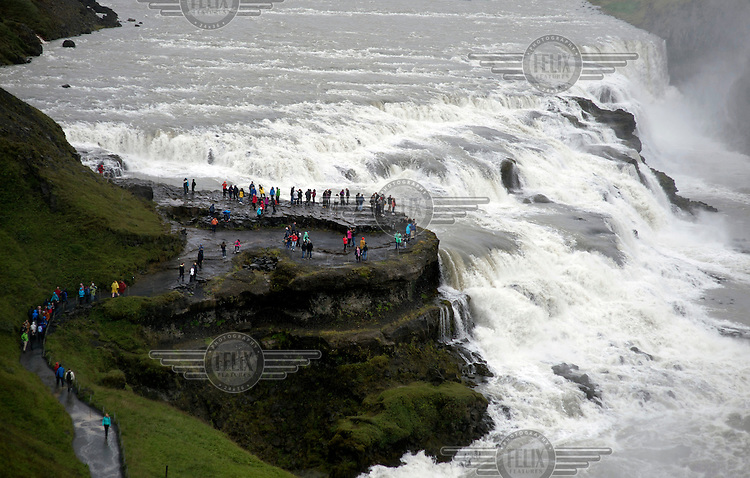Tourists at the Gullfoss waterfall on the Hvita River, a double cascade dropping a 32m.