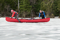Conor and Kim Mihell take a break from propelling their canoe over a frozen lake during an early spring trip to Lady Evelyn-Smoothwater Provincial Park in Ontario Canada.