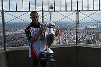 New York, USA. 23 April 2014.  Supercross motorcycle racer Mike Alessi  holds the trophy while they promote their motorcycle race during a visit to the Empire State Building in New York. Photo by Eduardo Munoz Alvarez/VIEWpress