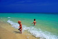 Two nude toddler boys, aged two, frolic in the surf at beautiful Lanikai Beach on windward Oahu.