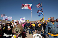 Searchlight, Nevada, March 28, 2010 - Tea Party supporters hold their hats during the national anthem during the first Tea Party Express rally in Searchlight, the hometown of Senate Majority Leader Harry Reid. Dubbed the Showdown in Searchlight, the event is located just north of town on private property near Reid's home. The raucous, but peaceful event was expected to draw 5,000 to 10,000 supporters, with actual estimates ranging from 7,000 to 8,000 - though party organizers said the numbers were as high as 13,000. The 20-day tour will wind through the United States ending up in Washington, D.C. on April 15 for a tax day rally. .