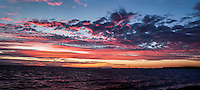 Two images merged into a single panoramic to capture the expanse of Sunset over San Francisco Bay.  In tiny silhouette on the horizon - the San Francisco skyline.