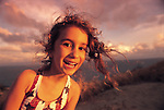 A young girl smiles as her hair blows in the wind on a beach at sunset