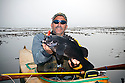 WA07100-00...WASHINGTON - Phil Russel with a black rockfish caught kayak fishing with a fly rod in the Strait of Juan De Fuca near Seal and Sail Rocks.