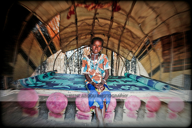In the Fulani village of Jolooga in northern Burkina Faso, a girl sits on a traditional bed in a house made of handwoven straw mats supported by thin sticks of wood.  Additional straw mats serve as a mattress.   The Fulani are traditionally nomadic pastoralists, crisscrossing the Sahel season after season, year after year, in search of fresh water and green pastures.  This house can be disassembled at will, the mats rolled up and loaded onto camel or donkey cart, and reassembled at a new location.  This is a dry season house.  When the rains come, the decorative mats will be stored safely away from water, and a different kind of straw house built.