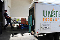 Phoenix, Arizona. October 18, 2012 - A United Food Bank employee unloads boxes of food donated from a delivery truck. The United Food Bank provides food to other community organizations that in turn provide meals and snacks to Arizona families in need. As the amount of food donations decreases, food banks such as the United Food Bank strive to keep up with hunger relief needs of 1 in 5 (20%) of Arizonans who are living in poverty and, based on figures of the Department of Health and Human Services. Photo by Eduardo Barraza © 2012