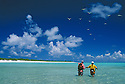 Fly fishing on reef flats at Bikini Atoll with seabirds flying overhead; guide Rod Bourke and fisherman Toshihiro Ishikawa; Marshall Islands, Micronesia.