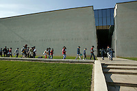 """25 April 2004 - Caen, France - Schoolchildren arrive at the Memorial museum in Caen, France, 25 April 2004. The text on the wall reads: """"pain broke me down fraternity picked me up""""."""
