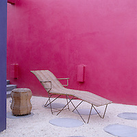 On the patio the walls have been painted in electric pink gloss paint and it is paved with large flat stones interspersed with gravel