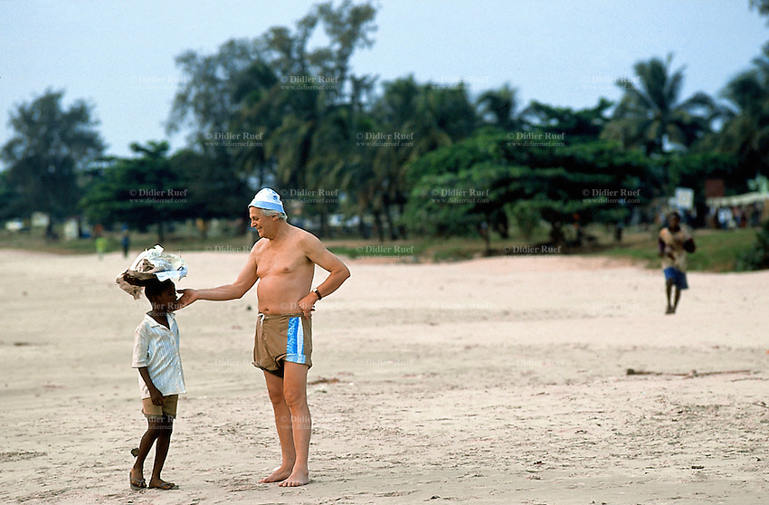 Sierra Leone. Freetown.  Aberdeen area. Lumley beach on the atlantic ocean. An old white man caresses in a fatherly way the cheeck of a young boy selling peanuts on the beach. © 2002 Didier Ruef
