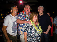 """HONOLULU, Turtle Bay Resort, North Shore, Oahu. - (Thursday, January 3, 2013) Greg Noll (USA) with wife Laura, Garrett MacNamara (HAW) and CBS reporter Anderson Cooper (USA), was the guest  speaker of Talk Story at Surfer The Bar tonight, Noll, nicknamed """"Da Bull"""" by Phil Edwards in reference to his physique and way of """"charging"""" down the face of a wave is an American pioneer of big wave surfing and is also acknowledged as a prominent longboard shaper. Noll was a member of a US lifeguard team that introduced Malibu boards to Australia around the time of the Melbourne Olympic Games. Noll became known for his exploits in large Hawaiian surf on the North Shore of Oahu. He first gained a reputation in November 1957 after surfing Waimea Bay in 25-30 ft surf when it had previously been thought impossible even to the local Hawaiians. He is perhaps best known for being the first surfer to ride a wave breaking on the outside reef at the so-called Banzai Pipeline in November 1964...It was later at Makaha, in December 1969, that he rode what many at the time believed to be the largest wave ever surfed. After that wave and the ensuing wipeout during the course of that spectacular ride down the face of a massive dark wall of water, his surfing tapered off and he closed his Hermosa Beach shop in the early 1970s. He and other surfers such as Pat Curren, Mike Stang, Buzzy Trent, George Downing, Mickey Munoz, Wally Froyseth, Fred Van Dyke and Peter Cole are viewed as the most daring surfers of their generation...Noll is readily identified in film footage while surfing by his now iconic black and white horizontally striped """"jailhouse"""" boardshorts and was interviewed by host Jodi Wilmott (AUS). . Photo: joliphotos.com"""
