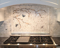 Plum Blossom with Butterflies, a hand cut stone mosaic shown in Calacatta Tia, Driftwood, Rosa Portagallo, Blue Bahia, Blue Macauba, and Lavender Mist, is used here in a custom kitchen backsplash.<br />