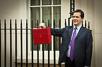 George Osborne, Chancellor of the Exchequer - 2011<br /> <br /> London, 23/03/2011. UK Prime Minister David Cameron leaves 10 Downing Street on Budget Day. He is followed by  the Chancellor of the Exchequer, George Osborne, who (followed by his team) shows the &quot;red box&quot; (Budget Box) containing the Budget for the fiscal year. In the meanwhile, outside the gates of Downing Street, protesters gather for a variety of demonstrations. The demands of protestors included an end to the Government budget cuts and austerity measures and a stop to cuts in the NHS.