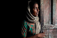 Shanno, 24, is 9 months pregnant with her 4th child as she stands at door of her rented 1 room house in a slum in Tonk, Rajasthan, India, on 20th June 2012. Shanno was married at the age of 17 and has had 4 successive pregnancies which affected her health and her children's health because she was unable to breastfeed them and was too poor to raise them properly. She had also given one of her sons to her sister at birth. She had also given one of her sons to her sister at birth. Her husband refuses to use contraceptives and she is not allowed to have an operation. Photo by Suzanne Lee for Save The Children UK
