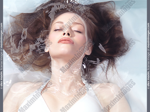 Natural look beauty portrait of a young woman lying relaxed in water with closed eyes. Beauty treatment concept.