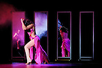 Expressive stage performance of a young woman dancing in front of mirrors with her reflection in purple clouds of smoke Show-ballet troup A-6 play Passion is Stronger Than Love in Kiev Ukraine April 2007 Black background Some parts of the image are blurred from motion