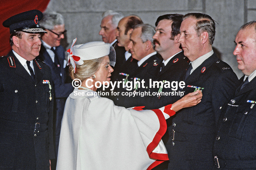 The Duchess of Kent, accompanied by Sir John Hermon, Chief Constable, RUC, presents long service medals to police officers at a ceremony in Antrim, N Ireland. Also in photo is the N Ireland Secretary of State, Douglas Hurd. 198501000008e<br />