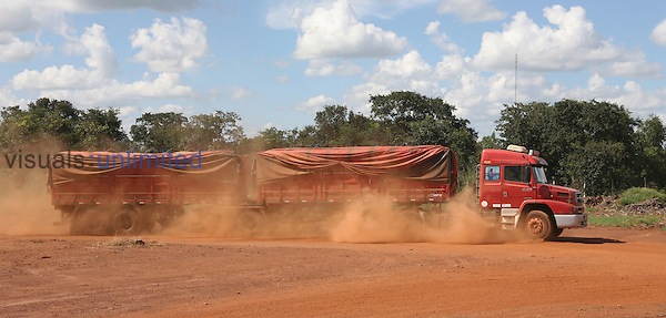 Truck carrying harvested crops over a dusty road in deforested rainforest land, Amazon Basin, Brazil