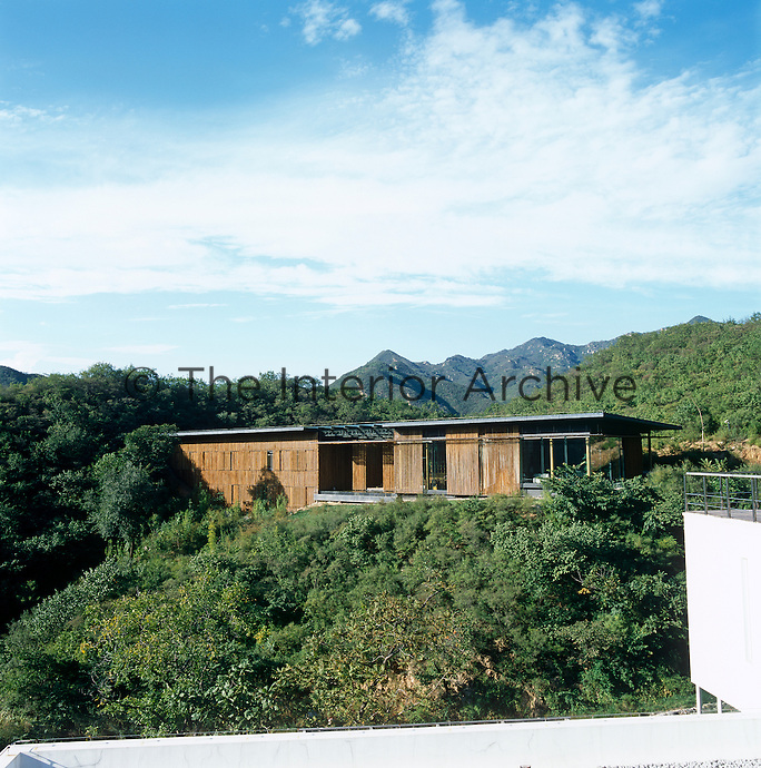 An exterior view of a villa designed by Kengo Kuma in Badaling, China with the Great Wall in the distance