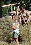 Foto: VidiPhoto<br /> <br /> ARNHEM - Hooitijd voor kinderen in het Nederland Openluchtmuseum in Arnhem dinsdag, zoals dat vroeger ging: met het hele gezin, in de hete zon en met de hand. Schudden, keren, wiersen en daarna optasten op een houten ruiter, zodat het hooi goed kan drogen. Het museumpark wil de kinderen zo laten ondervinden hoe zwaar het werk op het land vroeger was. Ze krijgen voor een half uur werk net zoveel betaald als eind 19e eeuw: 2 cent en een pannenkoek. Desondanks zijn de hooiwerkzaamheden razend populair onder de bezoekers.