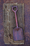 Worn and scratched red painted metal hand spade for use on beach or in garden lying on hessian on rusty metal sheet