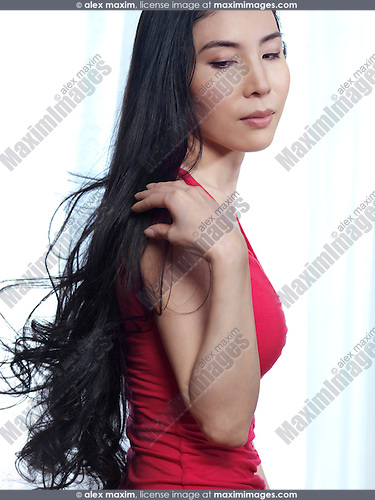 Beauty portrait of a young Japanese woman with long black hair at a window