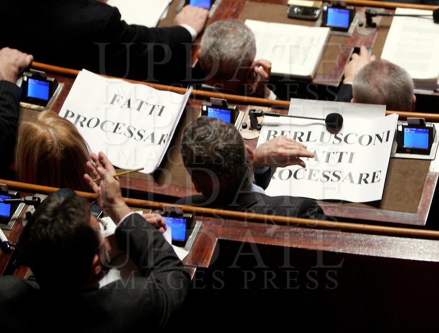 "I senatori dell'Italia dei Valori esibiscono cartelli di protesta durante una seduta nell'aula del Senato, a Roma, 20 gennaio 2010, in occasione del voto sul processo breve..Signs reading ""Berlusconi go to trial"" are seen on desks of Italia dei Valori's senators during a plenary session at the Senate, in Rome, 20 january 2010, prior to a vote on a bill that will shorten the length of trials..UPDATE IMAGES PRESS/Riccardo De Luca"